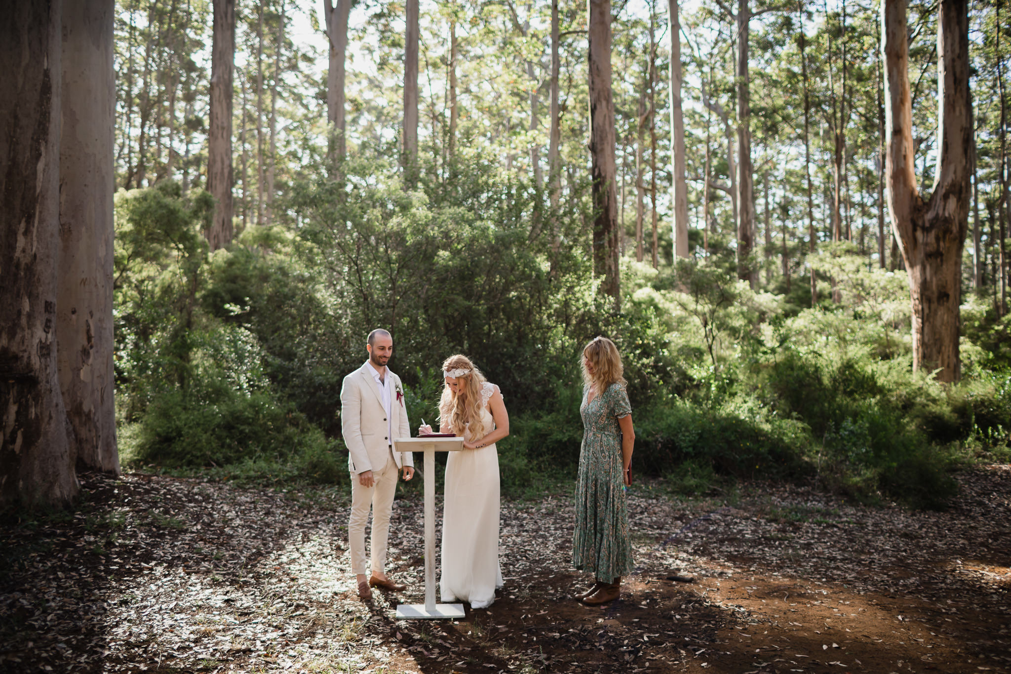 Bride and groom signing marriage certificate with golden light in Boranup forest