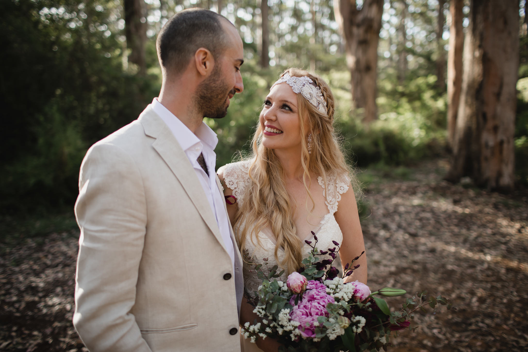 Bride with vintage dress and headpiece smiling at husband after elopement ceremony in Boranup forest