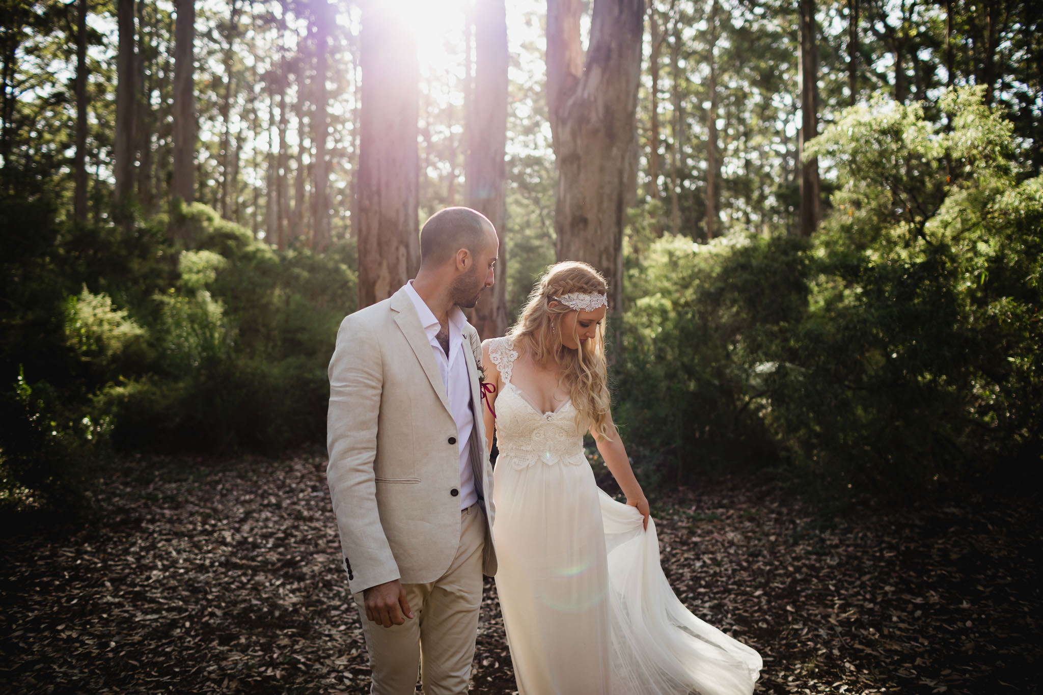 Bride swishing vintage style wedding dress with golden sunlight in Boranup forest