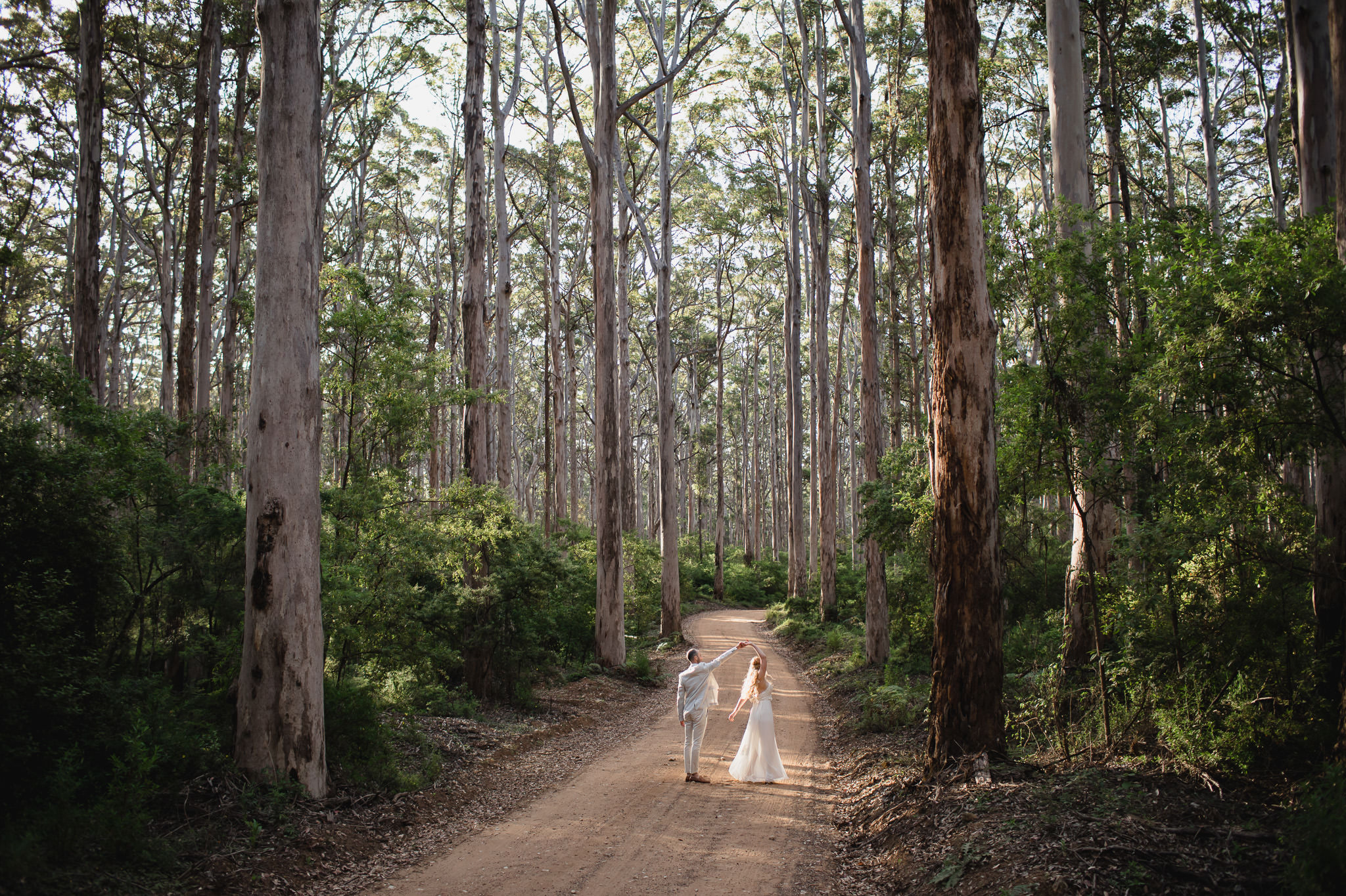 Bride and groom dancing on empty road n Boranup surrounded by karri trees after their wedding