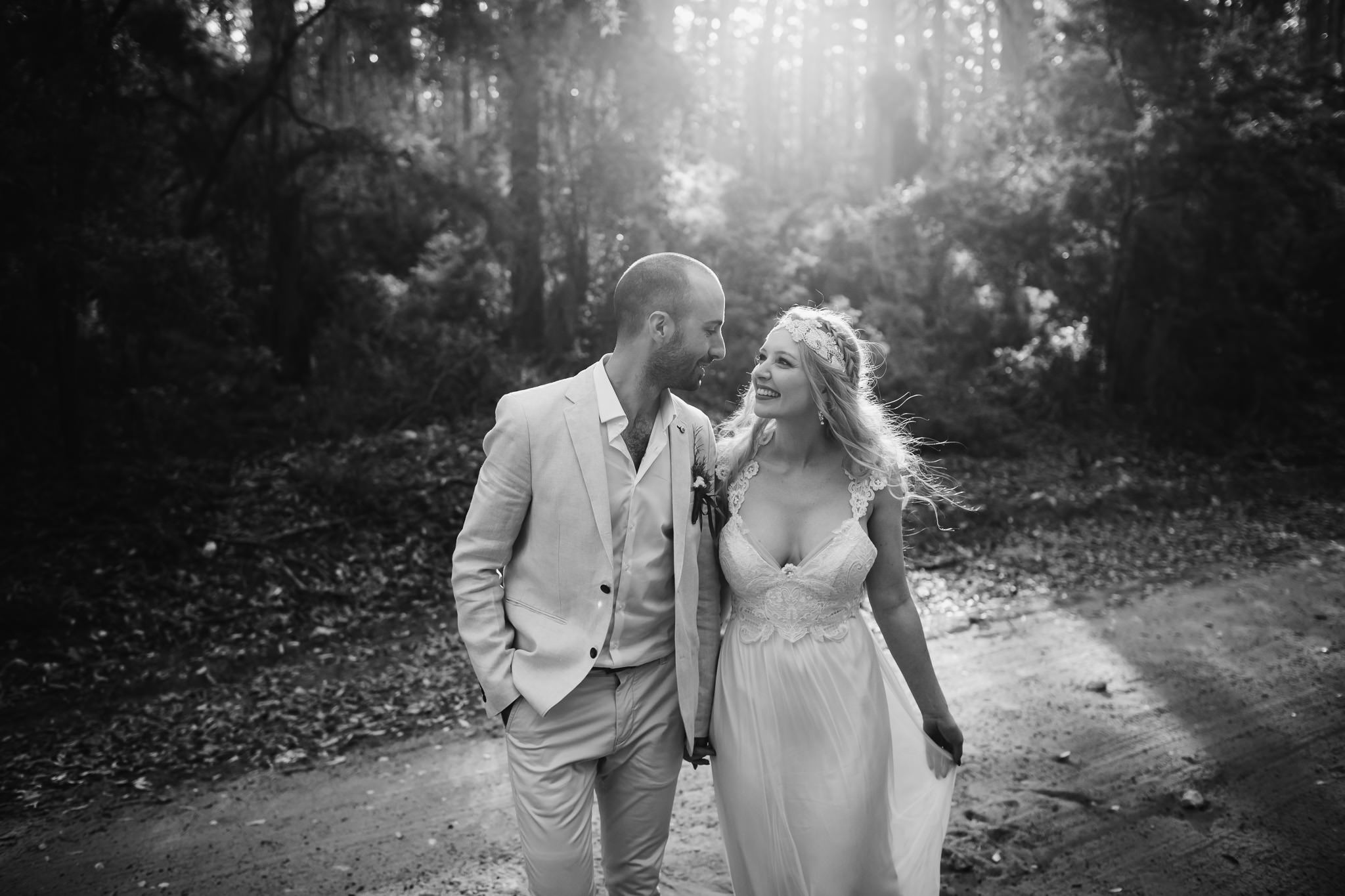Black and white photo of smiling couple walking on road in Boranup forest at their elopement wedding