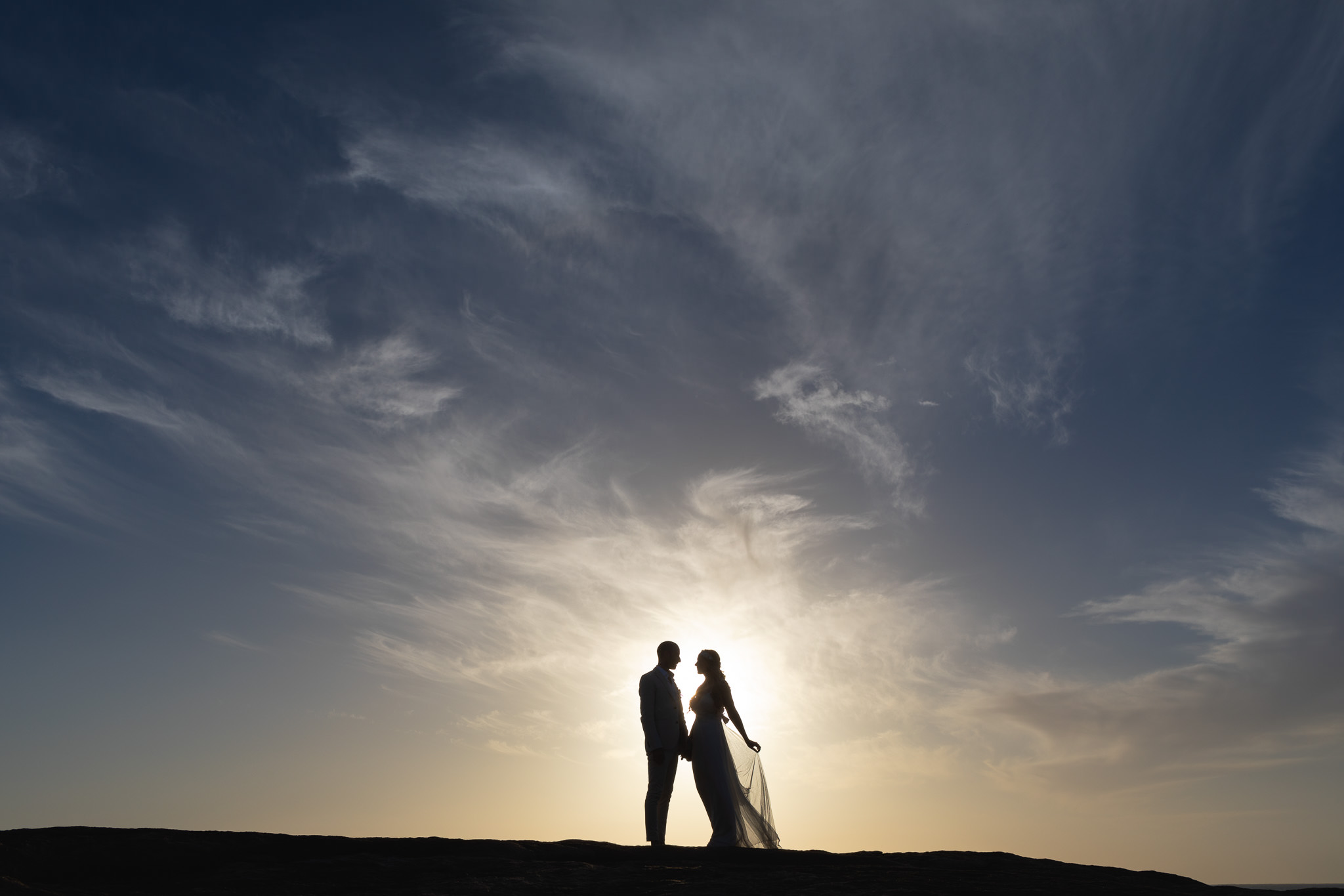 Wedding photo of silhouetted couple at sunset on the coast near Margaret River after their wedding