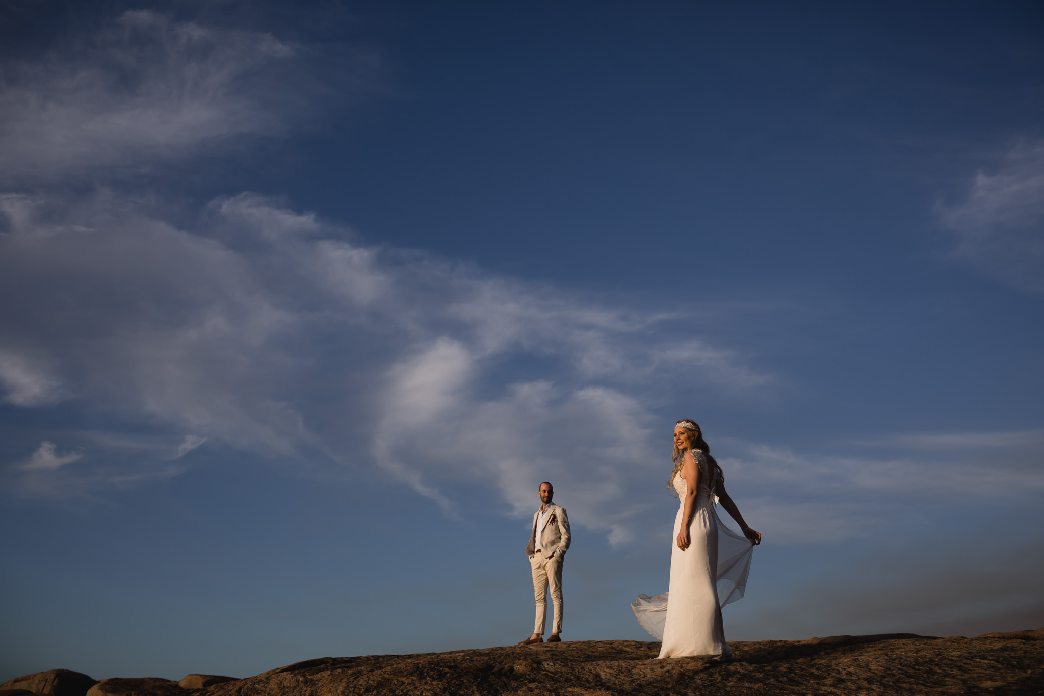 Bride and groom with soft golden light on them and blue sky behind during wedding photo session at sunset in Margaret River
