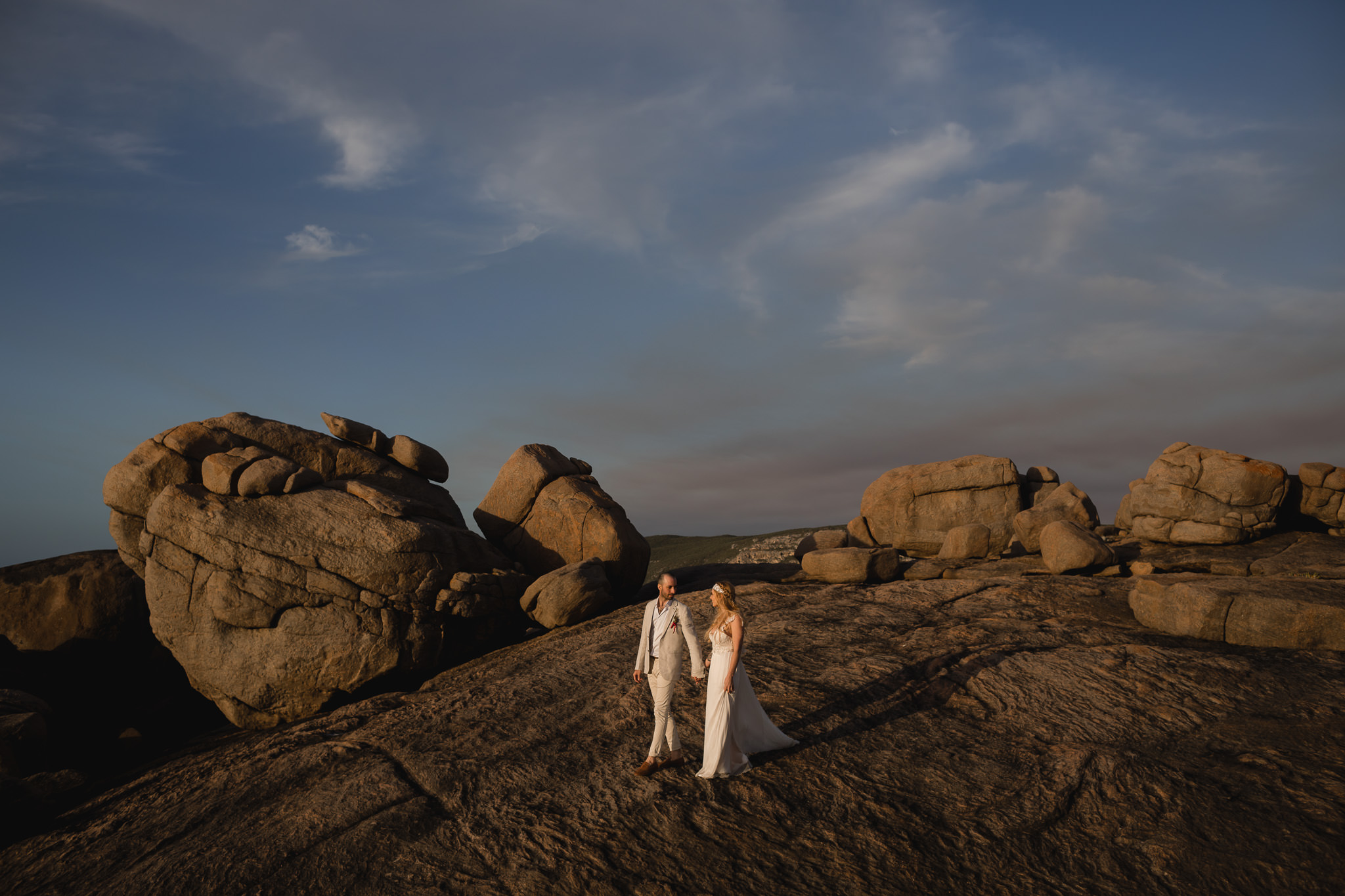 Wedding photo of bride and groom walking through amazing rock formations at coastline at sunset near Boranup forest