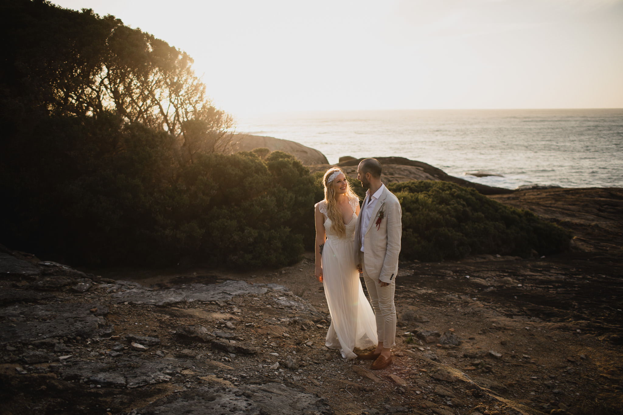 Golden light illuminating bride in vintage dress as she smiles at her husband at sunset at Contos Beach near Margaret River